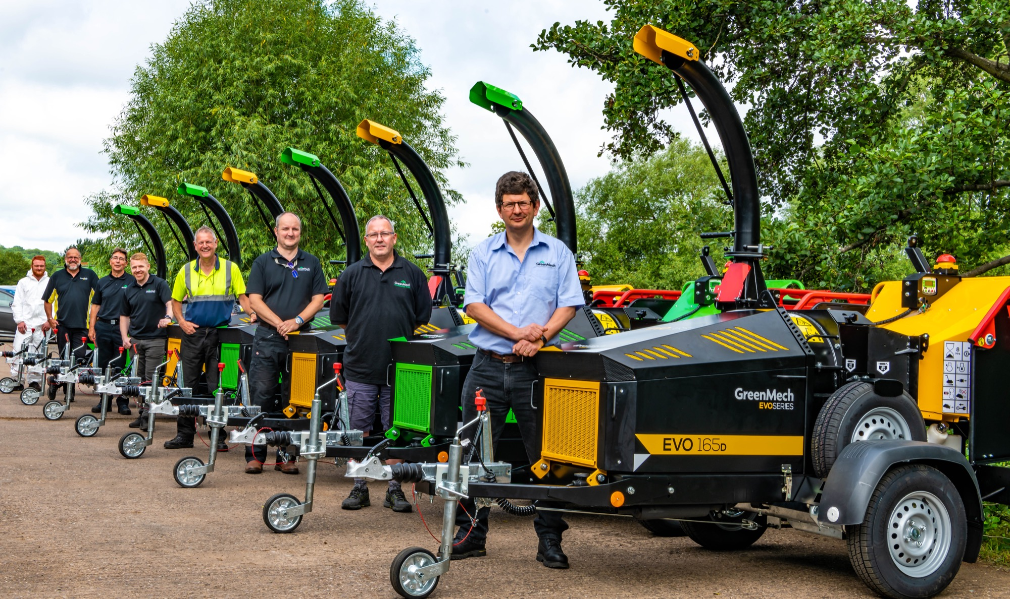 GreenMech members of staff stood next to Woodchippers in Alcester where they are manufactured